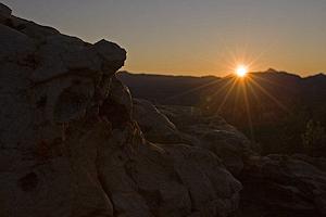 De zon zakt achter de bergen